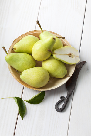 Palmleaf plate of sliced and whole pears (Pyrus), leaves and a knife on white wooden table