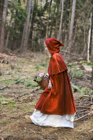 Girl masquerade as Red Riding Hood on the move in the wood LANG_EVOIMAGES