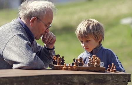 Germany, Rhineland-Palatinate, Leutesdorf, grandfather and grandson playing chess LANG_EVOIMAGES