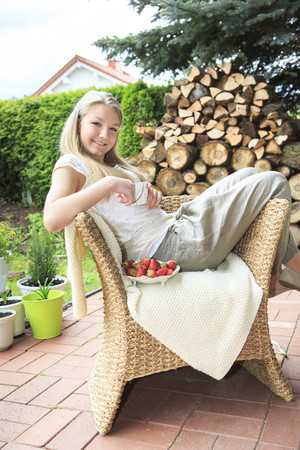 Portrait of smiling teenage girl sitting on wicker chair in the garden LANG_EVOIMAGES