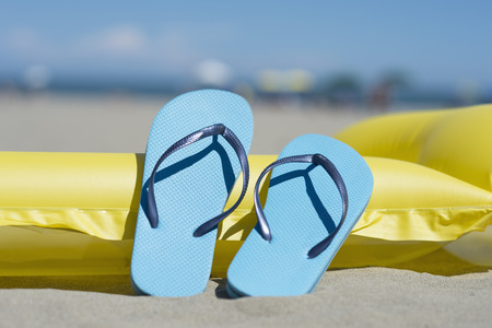 Pair of light blue flip-flops leaning on yellow airbed on the beach