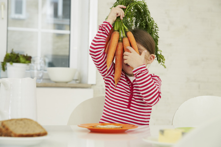 Germany, Munich, Girl sitting at table with bunch of carrots on head LANG_EVOIMAGES