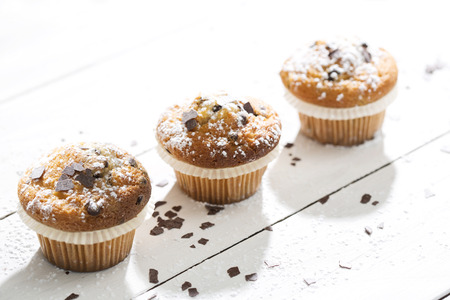 Three muffins in paper cups sprinkled with powdered sugar and chocolate shavings on white wooden table