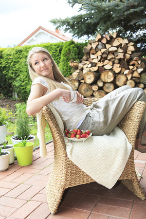 Portrait of teenage girl sitting on wicker chair in the garden
