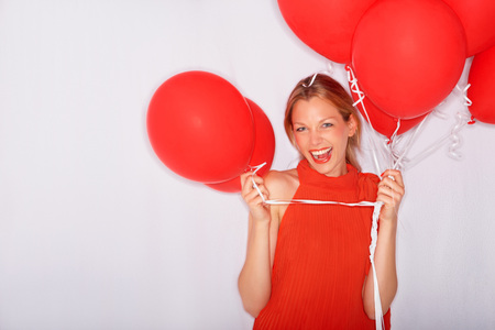 Excited young woman holding red balloons