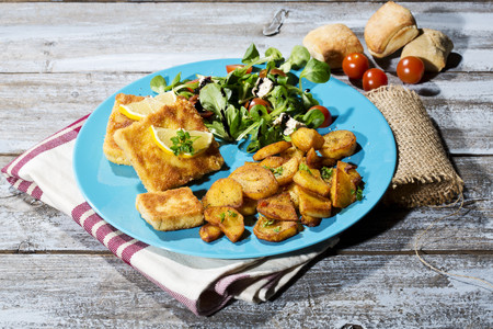 Baked organic tofu with fried potatoes and lambs lettuce with tomatoes and balsamico
