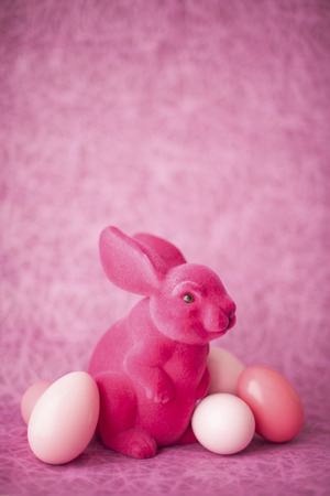 Pink Easter bunny with Easter eggs in front of pink background LANG_EVOIMAGES