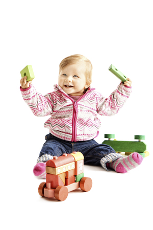 Toddler playing with wooden toy in front of white background
