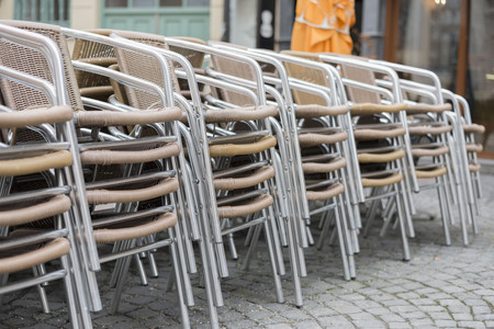 Stacked chairs of a restaurant in pedestrian area