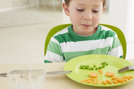Germany, Munich, Boy eating peas and carrots showing anthropomorphic face LANG_EVOIMAGES
