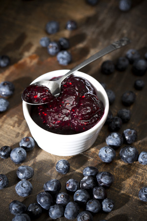 Bowl of blueberry and raspberry jam, spoon and blueberries on dark wooden table
