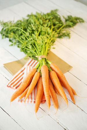 Bunch of organic carrots on cloth and white wooden table