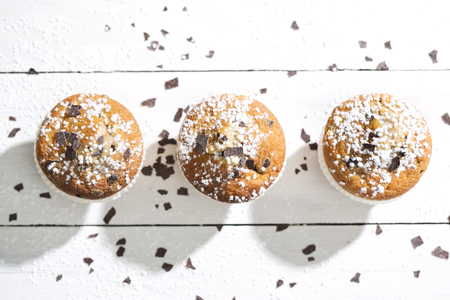Row of three muffins in paper cups sprinkled with powdered sugar and chocolate shavings on white wooden table, elevated view LANG_EVOIMAGES