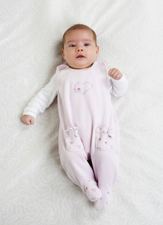 Female baby wearing pink rompers lying on white cloth