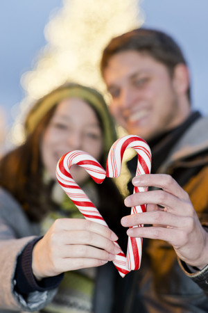 Germany, Berlin, young couple holding sugar canes formed as a heart LANG_EVOIMAGES