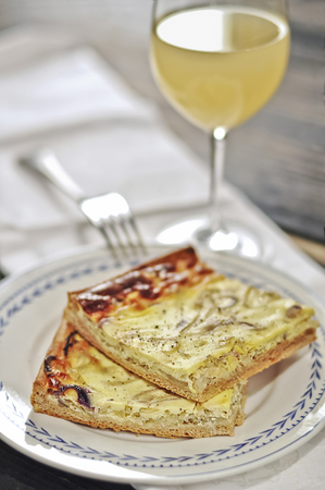 Plate with two pieces of onion tart and glass of Federweisser LANG_EVOIMAGES