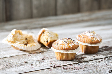 Two muffins in paper cups and half of a biten one in the background on grey wooden table