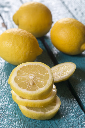 Whole and sliced lemons on blue wooden table LANG_EVOIMAGES
