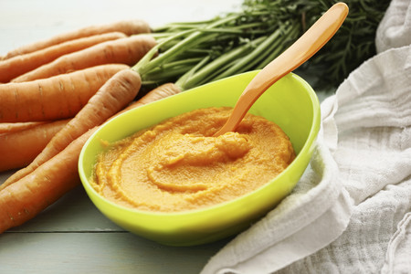 Bowl of carrot puree, carrots and cloth