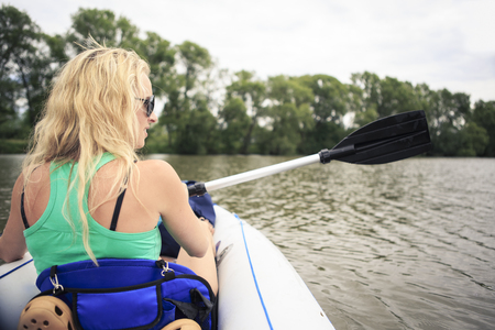Germany, Bavaria, Lichtenfels, Blond woman with boat on River Main LANG_EVOIMAGES