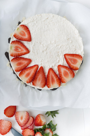 Garnishing cream cheese tart with strawberry slices, elevated view LANG_EVOIMAGES