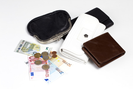 Different purses, banknotes and coins on white ground