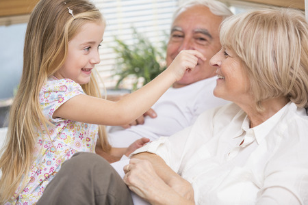 Senior couple and granddaughter relaxing on sofa in living room