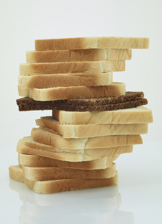 Single slice of black bread in a stack of toast bread