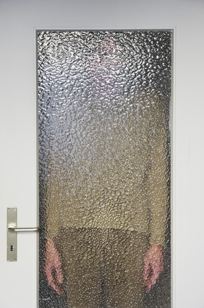 Man Standing Behind Closed Door With Ribbed Glass Pane Stock Photo