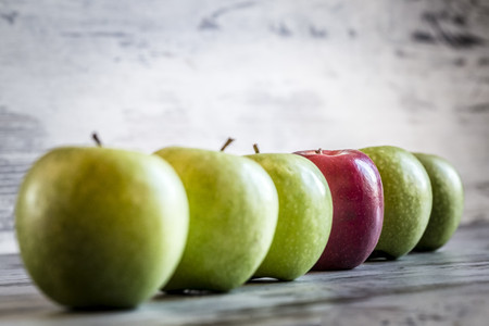 Red apple in a row of green apples LANG_EVOIMAGES