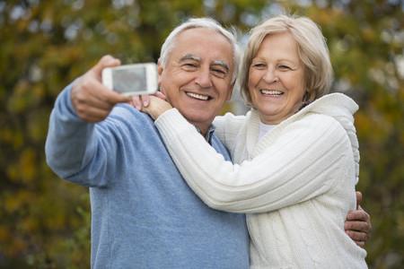 Portrait of smiling senior couple taking self-portrait with smartphone