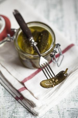 Pickled cornichons in preserving jar and fork LANG_EVOIMAGES