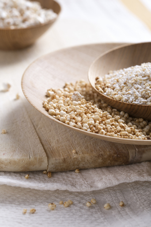 Bowls of puffed buckwheat, quinoa and amaranth on wooden board and kitchen towel