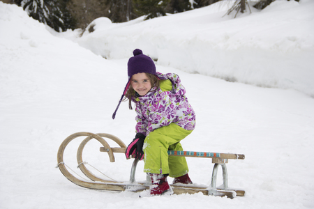 Austria, Carinthia, Gmuend, smiling little girl with sledge LANG_EVOIMAGES