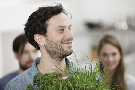 Smiling man with herbs in kitchen