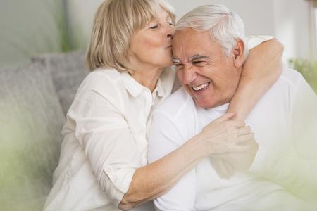 Senior woman kissing her husband in living room