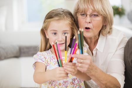 Mujer Senior y nieta mostrando lápices de colores