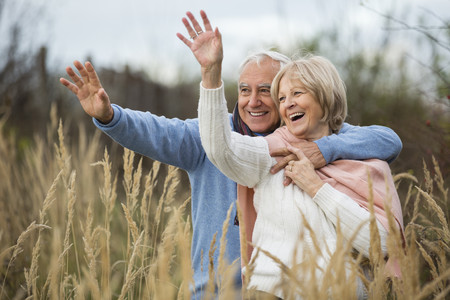 Portrait of happy senior couple having a walk and greeting someone