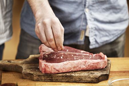 Man preparing steak in kitchen