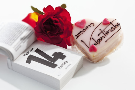 Red rose, petit four and tear-off calendar showing date of Valentines day on white ground LANG_EVOIMAGES