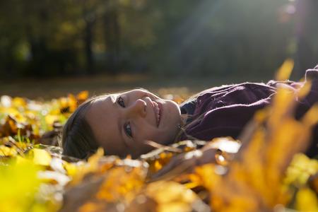 Portrait of smiling little girl lying on autumn leaves in park