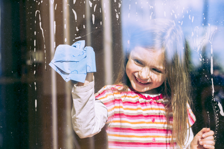 Portrait of smiling ittle girl cleaning window LANG_EVOIMAGES