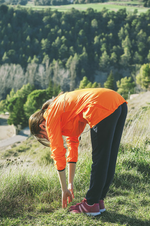 Young female jogger stretching LANG_EVOIMAGES