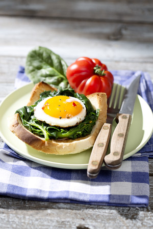 Fried eggs and spinach on toast with tomato