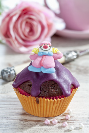 Decorated chocolate muffin in muffin paper on laid table
