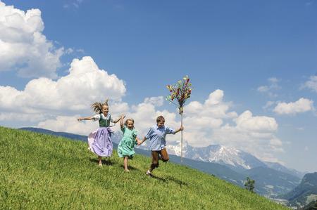 Austria, Salzburg State, Altenmarkt-Zauchensee, three children with Palmbusch running on alpine meadow