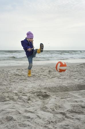 Denmark, Jutland, Vejers Strand, girl kicking ball on beach