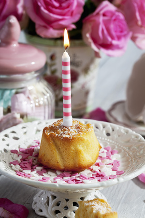Muffin with lighted birthday candle, glass of marshmallows, cup and pink roses on table