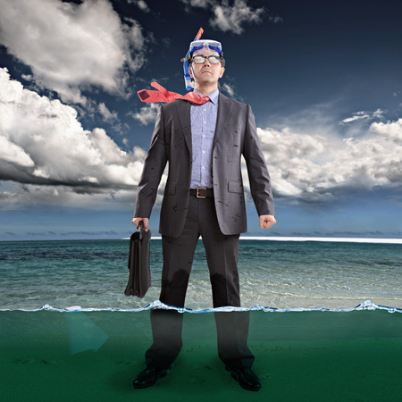 Businessman standing ankle-deep in water, wearing snorkel