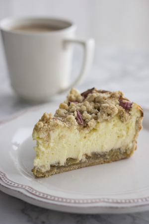 Piece of Rhubarb Cheese Cake on plate with cup of coffee